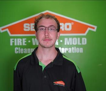 Man in front of green wall with orange SERVPRO logo.