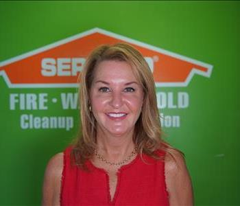 A woman standing in front of a green wall with a SERVPRO logo.